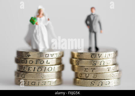 Close up/macro model stock photo depicting married husband and wife on £1 pound coin stack - Stock Photo
