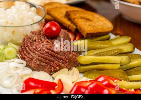 Raw beef Steak tartare with onion and toast - Stock Photo