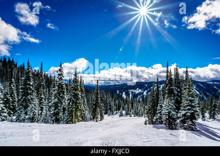 Bright sun and blue sky on the ski hills at Sun Peaks village  in the Shuswap Highlands of British Columbia - Stock Photo