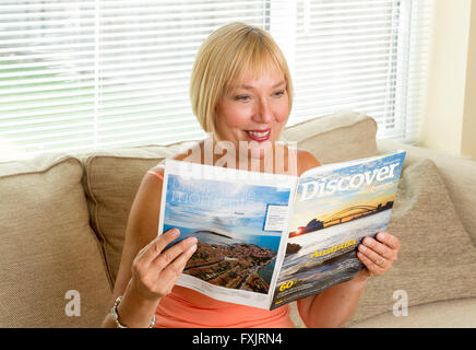 woman reading a travel guide magazine - Stock Photo