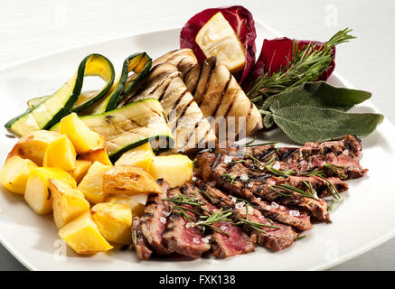 Single serving of rare cooked steak slices, baked yellow potato, eggplant and squash with herbs on plate - Stock Photo