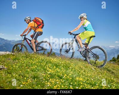 Man 40-45 years and woman 35-40 years with helmets cycle with their mountain bikes, Zirbenweg, Patscherkofel, Innsbruck, - Stock Photo
