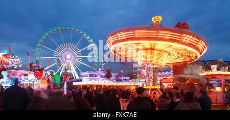 Ferris wheel with swing caroussel at dusk, fun fair Bremer Freimarkt, Bremen, Germany - Stock Photo