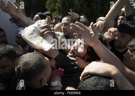 Gevgelija, Greece. 16th Apr, 2016. Refugees fight over bread as thousands of migrants remain stranded and hungry - Stock Photo