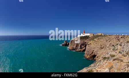 Portugal, Algarve: Lateral  and distant view of cliffs and lighthouse at Cape St. Vincent - Stock Photo