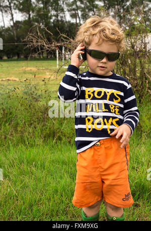 Photo of young boy with sunglasses talking to a camera lens cap pretending it is a mobile phone in a rural setting - Stock Photo