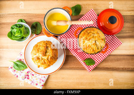 Spanakopita - Greek spinach pie with feta and ricotta, baked in cast iron pots, with melted butter - Stock Photo