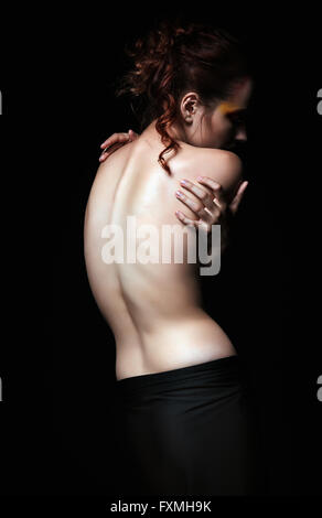 Dramatic portrait of a sad young woman among the dark. Rear view - Stock Photo