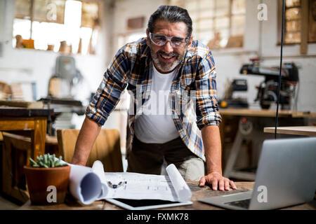 Portrait of carpenter with blueprint - Stock Photo