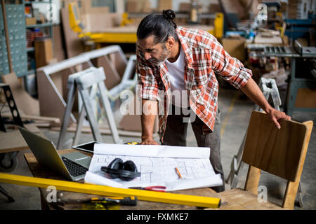 Carpenter working on blueprint while looking away stock photo woodworkers with timber carpenter looking at laptop while working on blueprint stock photo malvernweather Images