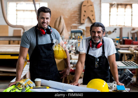 Portrait of two carpenters standing together in workshop - Stock Photo