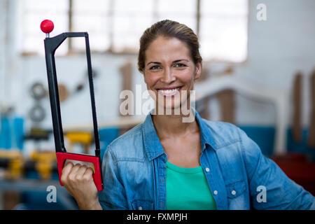 Happy female carpenter holding coping saw - Stock Photo