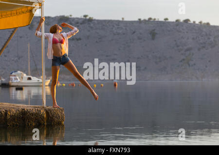 Balancing above sea teenager girl watching sunset outdoors Summer coming welcome welcoming single stand standing - Stock Photo