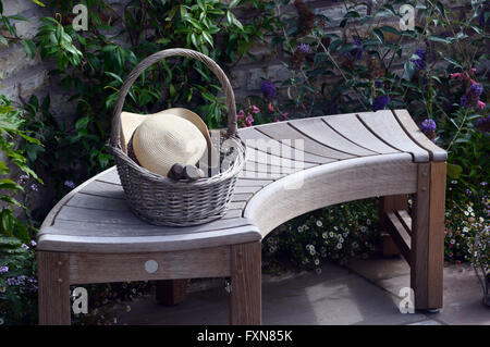 Curved Wooden Bench with Wicker Basket, Hat and Trowel on Display at the Southport Autumn Flower Show. Lancashire - Stock Photo