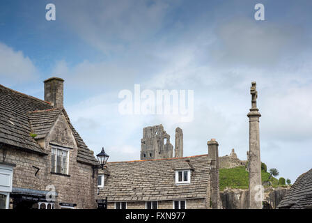 Corfe Castle seen above buildings in the village of the same name in Dorset, England, UK - Stock Photo