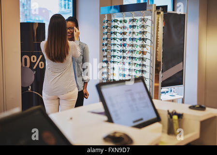 Saleslady assisting a customer in a store trying on eyeglasses with a view of a computer terminal in the foreground - Stock Photo
