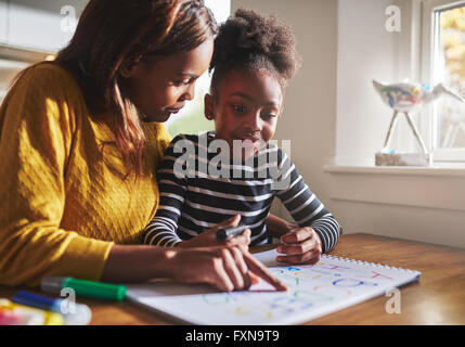 Black mother learning her daughter the alphabet at home using colours to draw - Stock Photo