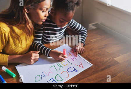 Learning the alphabet at home with her mom, black mother and child - Stock Photo