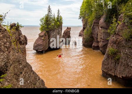 Hopewell Rocks kayaker beach at high tide with kayak, kayaker in water. Bay of Fundy, New Brunswick, Canada - Stock Photo
