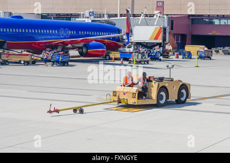 Workers reposition an aircraft tug after pushing back a jet airpliner for take off.  Las Vegas, Nevada - Stock Photo