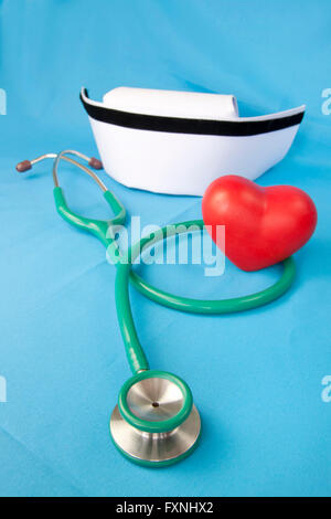 Stethoscope, nurse hat and heart red ceramic on blue fabric. - Stock Photo