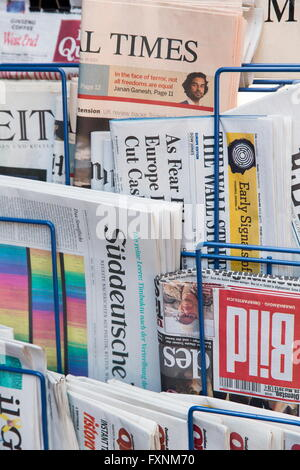 Various newspapers in a news rack - Stock Photo
