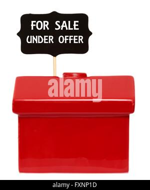 Red house with for sale under offer sign - Stock Photo