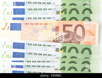 A fifty euro note between many hundred euro notes - Stock Photo