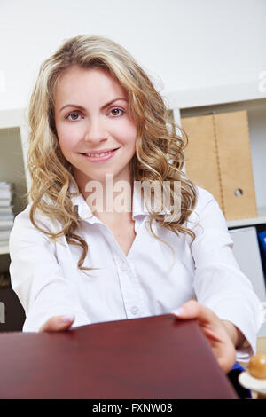 Attractive smiling woman offering application portfolio during a job interview - Stock Photo