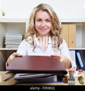 Smiling blonde woman in office offering her application material - Stock Photo