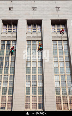 Window cleaners suspended on building, Wale Street, Cape Town, South Africa. - Stock Photo
