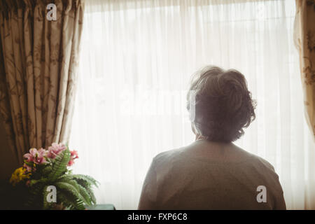 Senior woman looking out of the window - Stock Photo