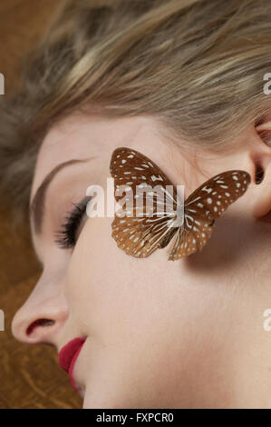 Young woman sleeping with a butterfly on her face - Stock Photo