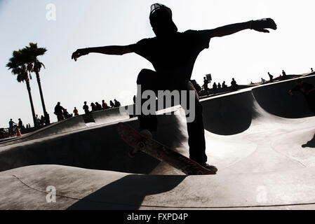 Young man skateboarding in skate park - Stock Photo
