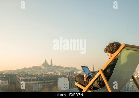 Man relaxing on rooftop terrace with digital tablet - Stock Photo