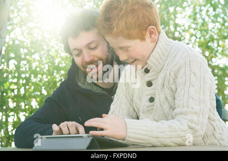 Father and son looking at digital tablet together - Stock Photo