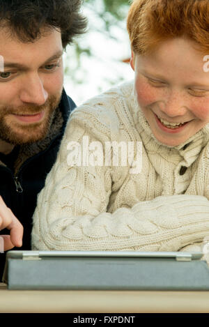 Father and son using digital tablet together - Stock Photo