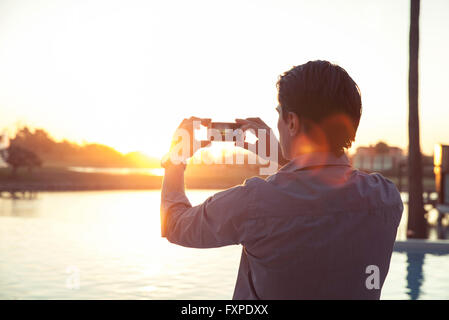 Man photographing sunset with smartphone - Stock Photo