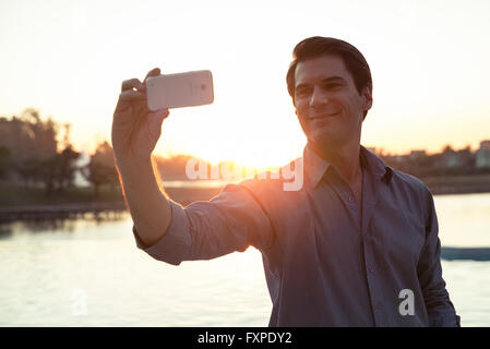 Man using smartphone to photograph himself in front of sunset - Stock Photo