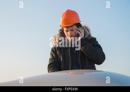 Construction worker talking on cell phone - Stock Photo