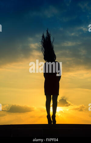Full length silhouette of a woman flicking hair against a dramatic sunset - Stock Photo