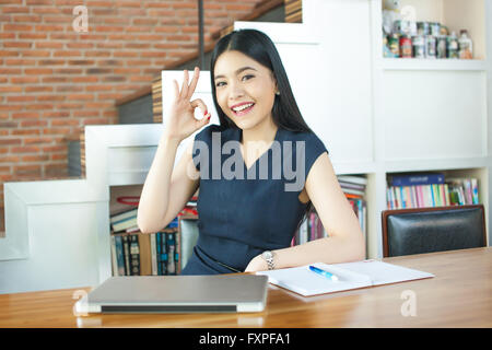 Asian Young Woman sitting with laptop computer and ok sign - Stock Photo