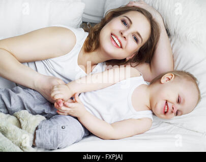 happy beautiful mother with her one year old son, studio shot - Stock Photo