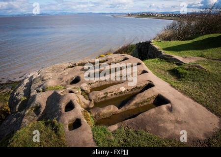 Unusual rock cut graves next to the ruins of St. Patrick's Chapel overlooking Morecambe Bay, Heysham, Lancashire, - Stock Photo