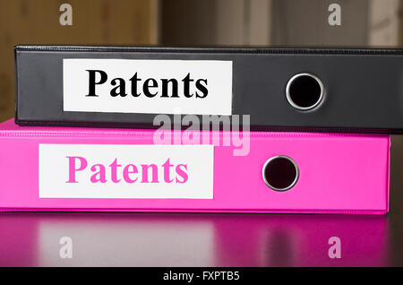 Bright office folders over dark background and patents text concept - Stock Photo