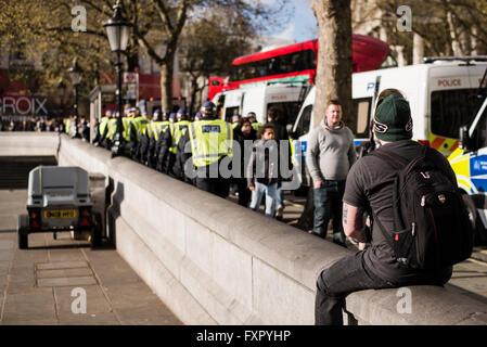 Trafalgar Square, London, UK. 16th Apr, 2016. Photographer checking out a line of policemen Credit:  Daniele Roversi/Alamy - Stock Photo