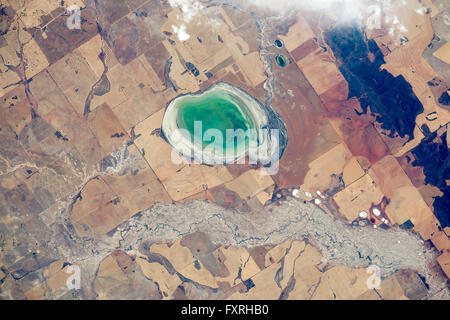 International Space Station view looking down from space at a small turquoise colored seasonal lake partly filled - Stock Photo