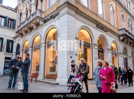 Venice Italian people locals and tourists shopping. Man pushing baby stroller in front of Ferragamo and Gucci fashion - Stock Photo