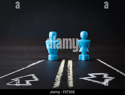 Male and female figurines standing on a two way lane road. Relationship concept. - Stock Photo