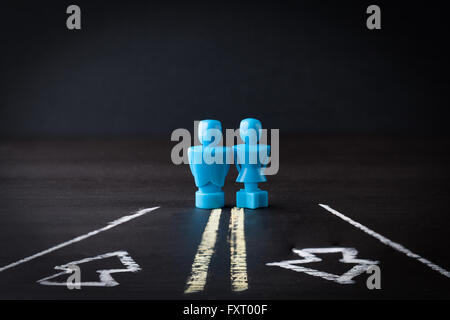 Male and female figurines standing on a two way lane road. Relationship and communication concept. - Stock Photo